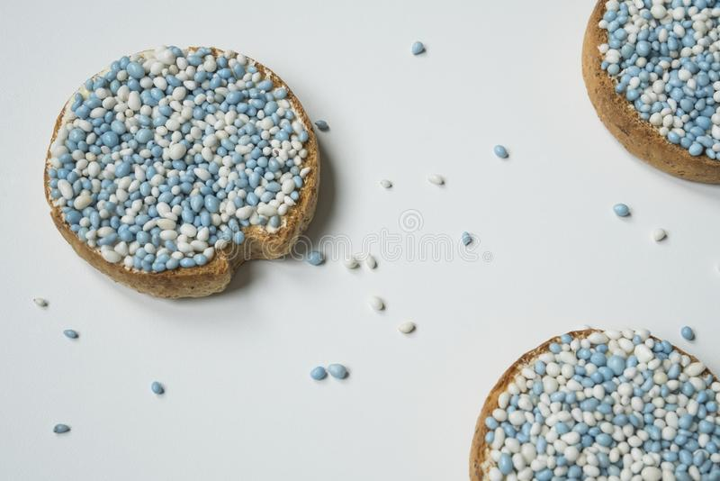 Flat lay rusk with Dutch aniseed balls called `muisjes`. Announcement when a baby boy is born. Rusk with blue aniseed balls, muisjes. Tradition in The royalty free stock photos