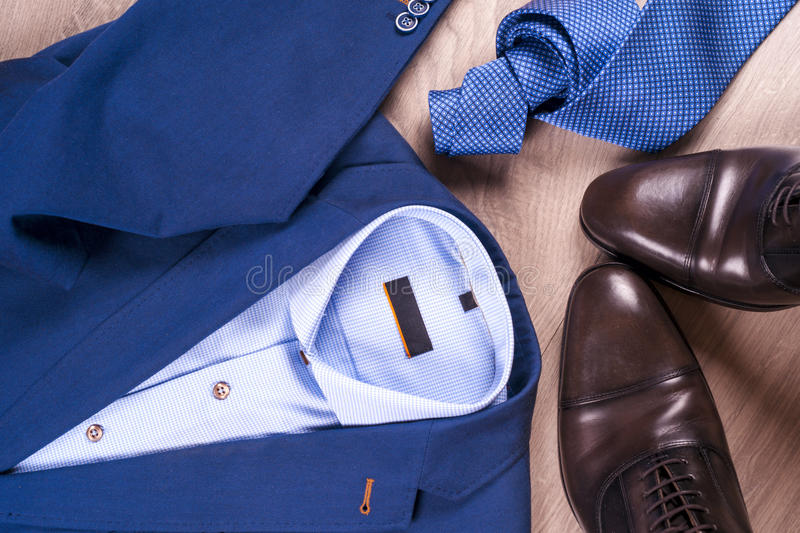 Flat lay set of classic mens clothes such as blue suit, shirts, brown shoes, belt and tie on wooden background. stock images