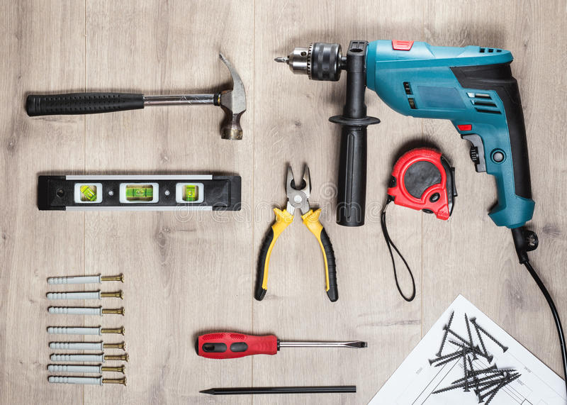 Flat lay Set of construction tools to repair on a wooden surface: drill, hammer, pliers, self-tapping screws, roulette stock photo