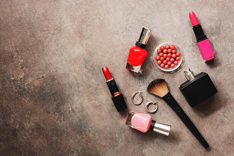 Flat lay set of decorative cosmetics, blush, brush, nail polish, lipstick and perfume on a dark rustic background. Top view, copy stock photo