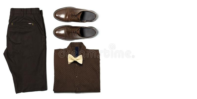 Flat lay set Men`s classic clothing, blazer jacket pants shirt bow tie leather shoes isolated items on white background top view. royalty free stock photo