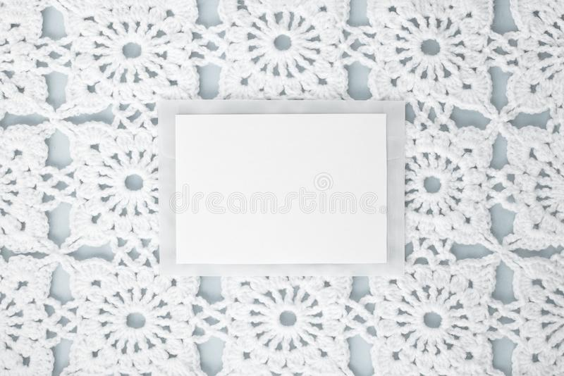 Flat, lay, a sheet of paper for text on a blue background with crocheted white vintage lace, winter theme, square ornament.  royalty free stock photography