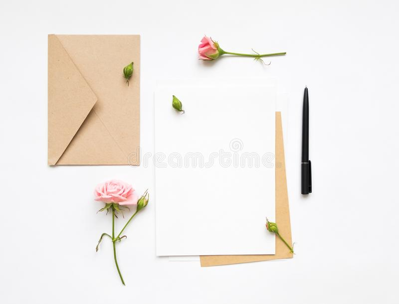 Letter and eco paper envelope on white background. Invitation cards, or love letter with pink roses. Holiday concept, top view, fl. Flat lay shot of letter and stock photo