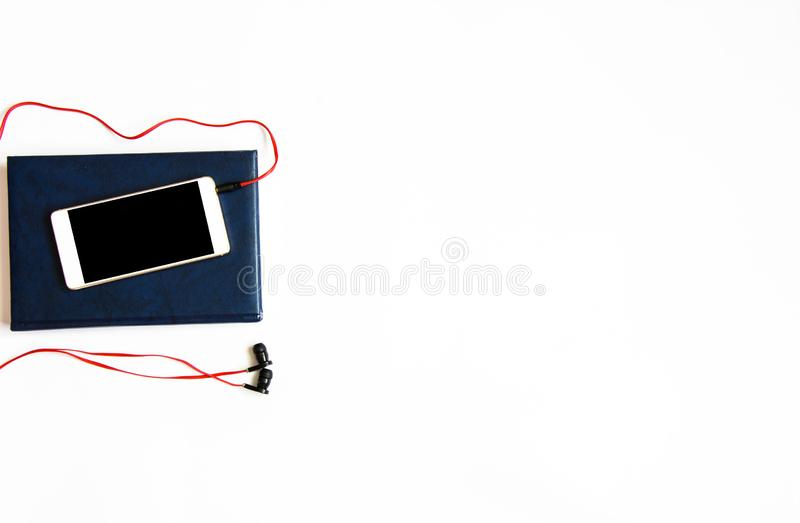 Flat lay shot of notebook, smartphone and earphones on white. Copy space stock photo
