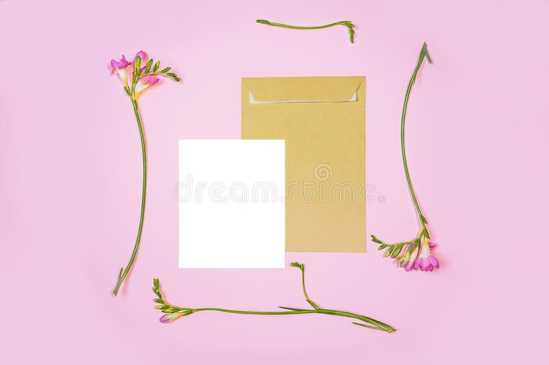 Flat lay shot of white letter sheet and eco paper envelope on pink background. Invitation cards or love letter with pink lily. Flat lay shot of white letter royalty free stock images