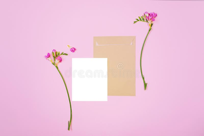 Flat lay shot of white letter sheet and eco paper envelope on pink background. Invitation cards or love letter with pink lily. Flat lay shot of white letter royalty free stock photo