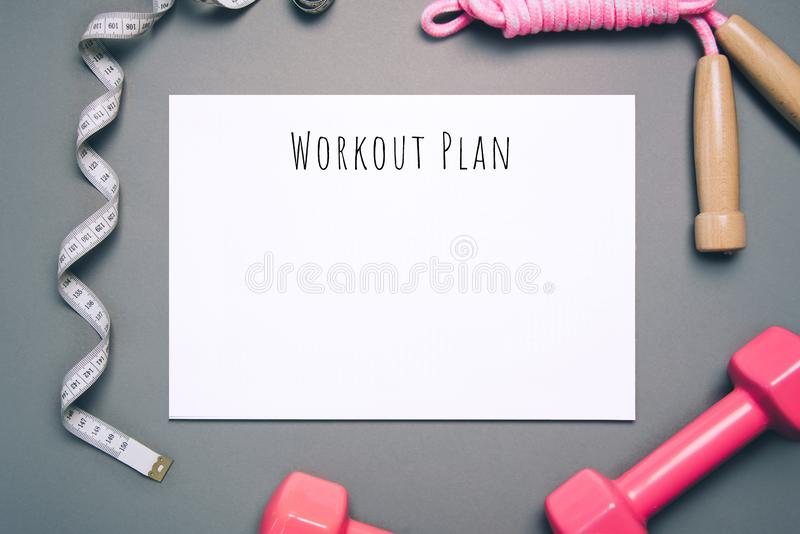 Flat lay shot of workout plan on gray background. royalty free stock photo