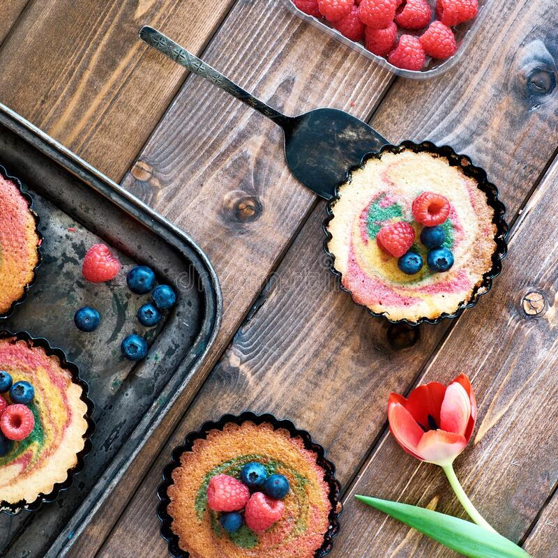 Flat lay with small parrotot cakes decorated with raspberry and stock photo