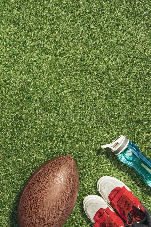 Flat lay with sneakers, rugby ball and water bottle. On green lawn stock photography