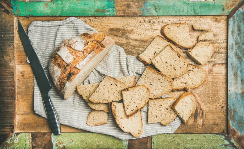 Flat-lay of sourdough wheat bread cut in slices in tray. Flat-lay of freshly baked sourdough wheat bread loaf halved and cut in slices on board over linen napkin royalty free stock photo