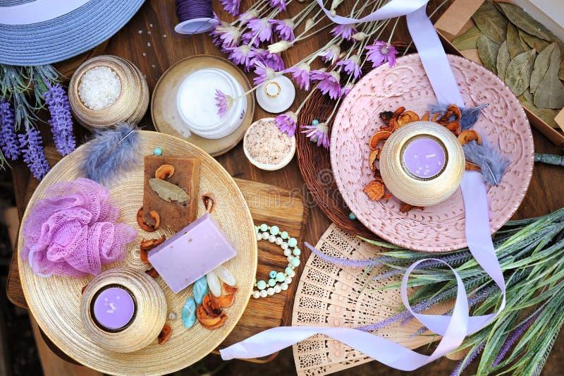 Flat lay spa accessories, handmade artisan soap, fresh flowers, wisp of bast, candles, bath salt. Etc. Wooden backdrop royalty free stock photo