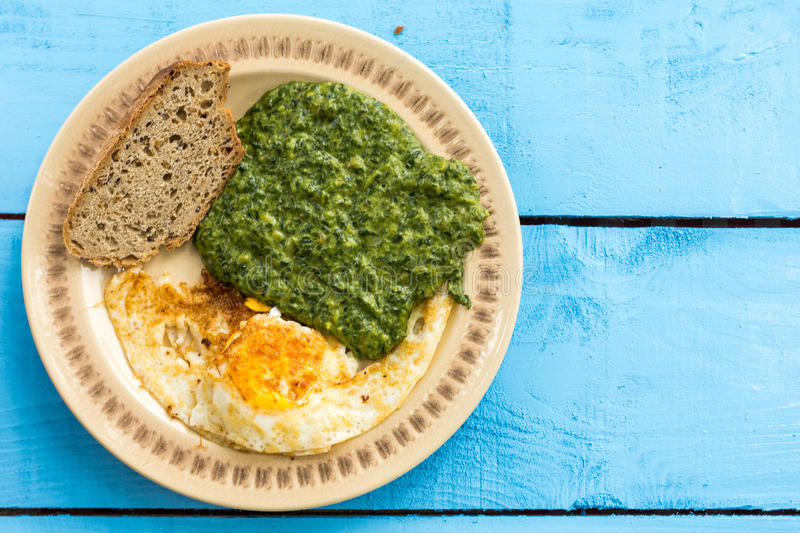 Flat lay spinach with fried eggs and slice of black bread royalty free stock images