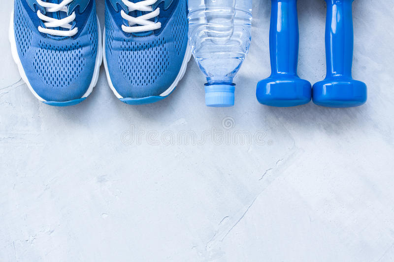 Flat lay sport shoes, bottle of water and dumbbells royalty free stock photos