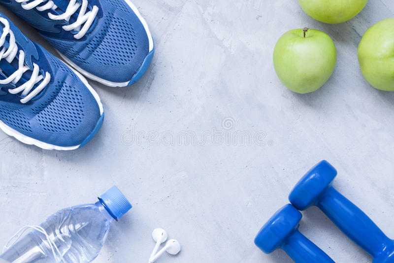 Flat lay sport shoes, dumbbells, earphones, apples, bottle of wa royalty free stock images
