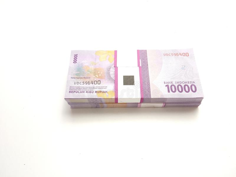 Simple Photo flat lay, stack of bundle Ten Thousand Rupiah Indonesia Money, at White Background. Flat lay, stack of bundle Ten Thousand Rupiah Indonesia Money stock photography