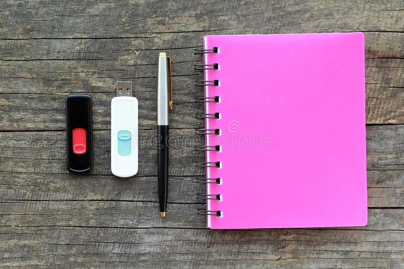 Flat lay of stationery, namely pink bounded note book, pen and two usb flash drives on gray wooden table royalty free stock images