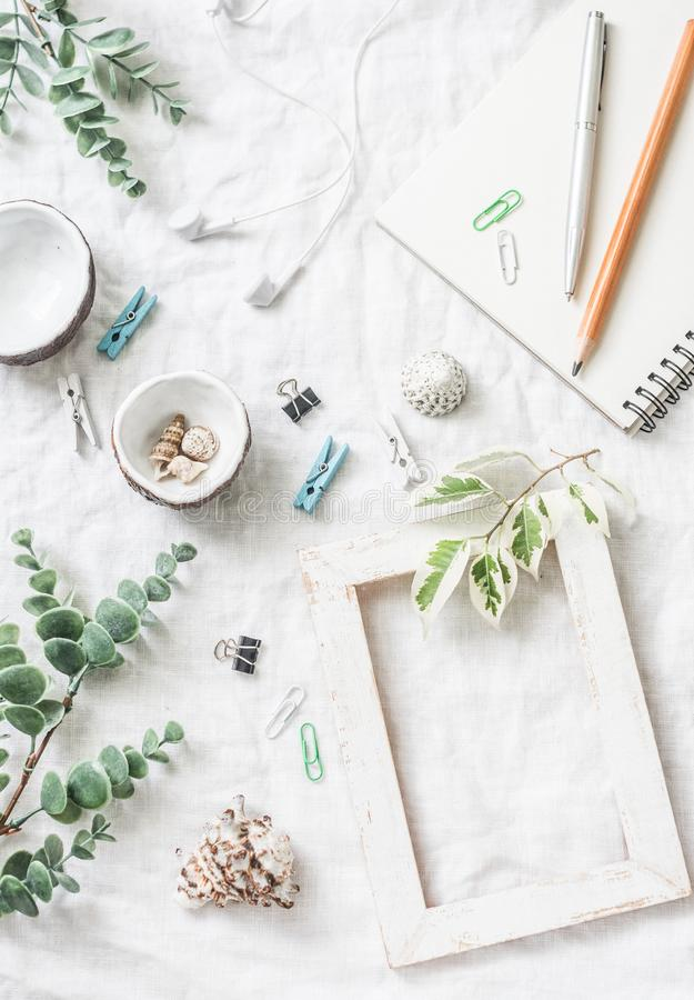 Flat lay still life of homemade crafts work table with accessories - wooden photo frame, flowers, seashells, paper clips, notebook. Pencil, decorative stock photography