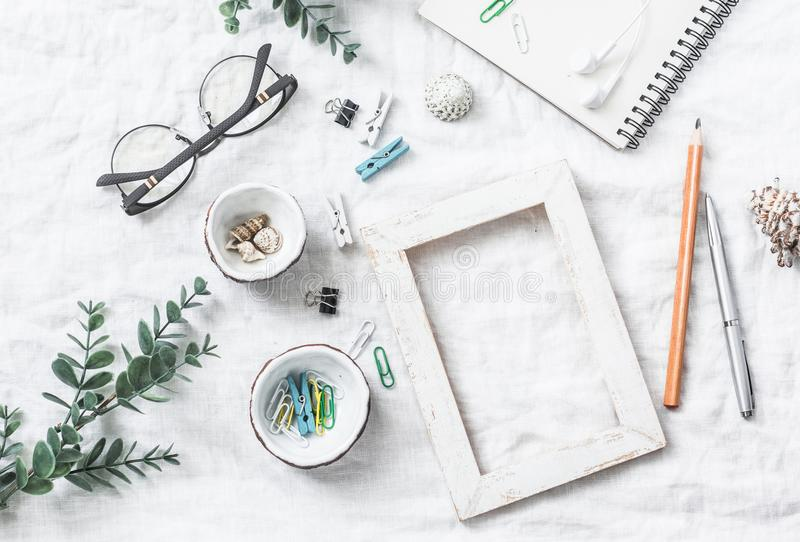 Flat lay still life of homemade crafts work table with accessories - wooden photo frame, flowers, seashells, paper clips, notebook. Pencil, decorative royalty free stock images
