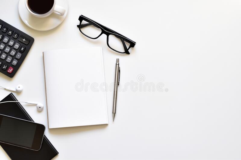 Flat lay style, Top view white table desk with copy space has black coffee, book, pencil, glasses, mobile is elements. royalty free stock photo
