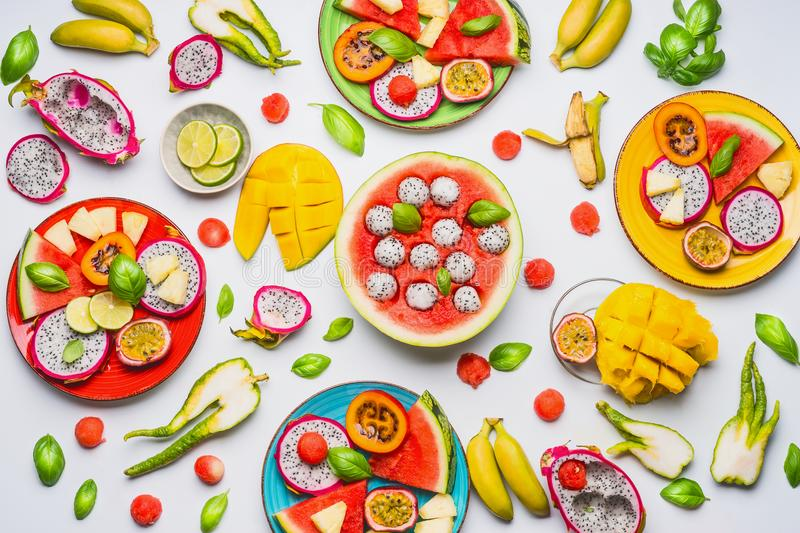 Flat lay of summer various colorful sliced tropical fruits and berries in plates and bowls on white background royalty free stock photo