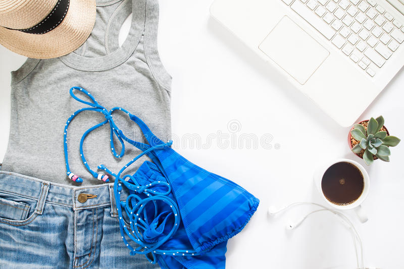 Flat lay of summertime clothing with blue stripe bikini, laptop. And cup of coffee on white background stock photos