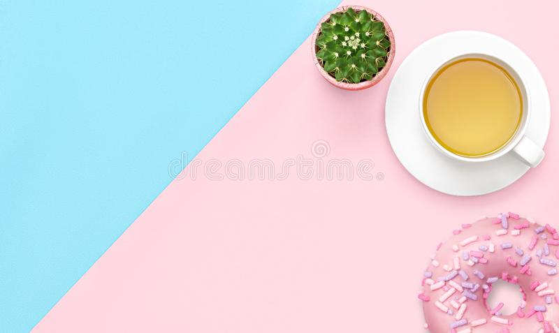 Flat lay sweet food concept breakfast of tea mug and donut on office work table. Top view. Copy space royalty free stock image