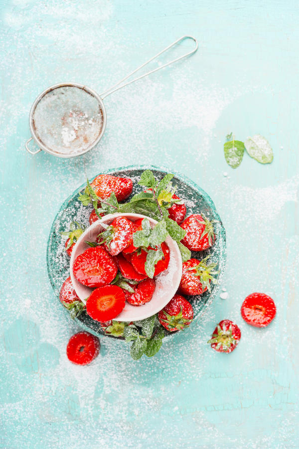 Flat lay with Sweet sliced Strawberries in bowls with icing sugar on light blue background. Top view stock photo