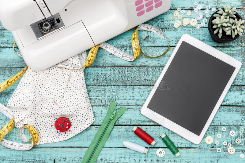 Digital tablet and tailoring items on table. Flat lay with tablet with blank screen, sewing machine and various tailoring items on wooden surface royalty free stock images
