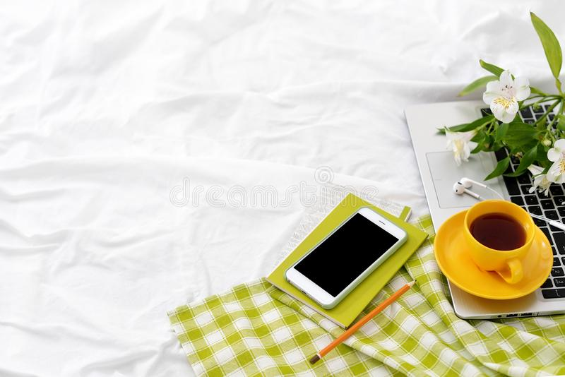 Flat lay tablet, phone, yellow cup of tea, laptop and flowers on white blanket with green napkin stock photo