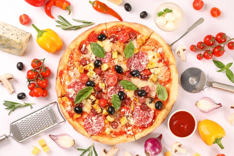 Flat lay. Tasty pizza, ingredients and kitchen supplies on white. Background royalty free stock image