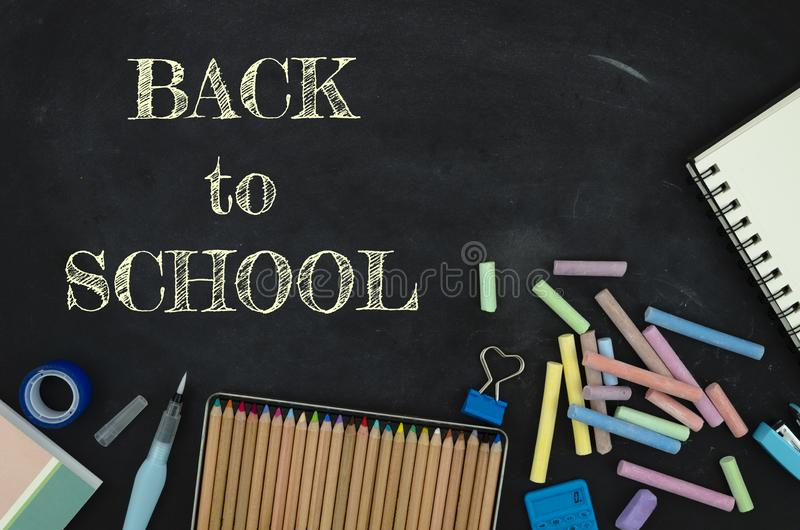 Flat lay tationery, notepads, pencils and clips over classroom blackboard with white chalk sign. Back to school concept.  stock photo