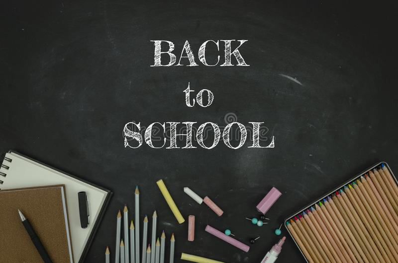Flat lay tationery, notepads, pencils and clips over classroom blackboard with white chalk sign. Back to school concept.  royalty free stock photos