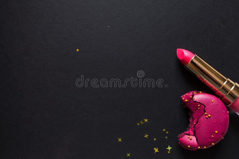 Flat lay template, in glamorous chic style, black background, scarlet lipstick and gold sequins. stock image