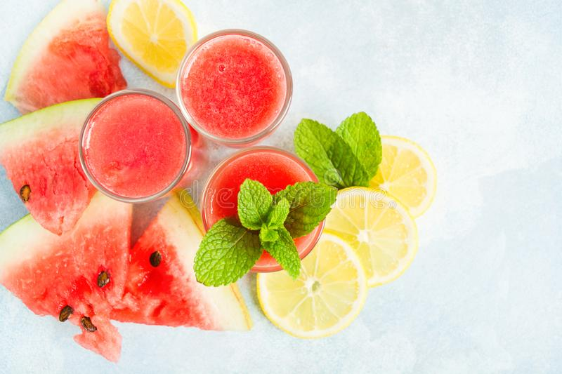 Flat lay with three glass of watermelon mojito on th blue background royalty free stock photos
