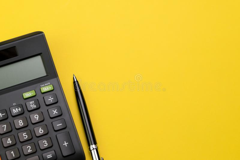 Flat lay or top view of black pen with calculator on vivid yellow background table with blank copy space, math, cost, tax or stock image