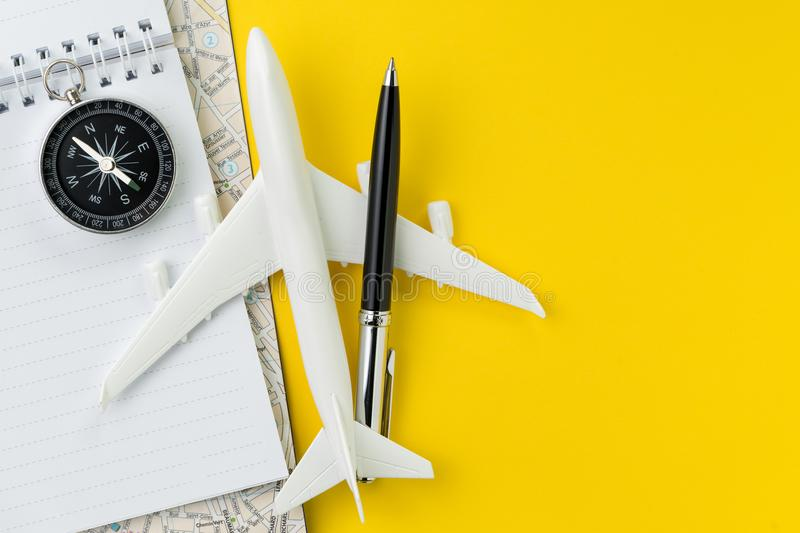 Flat lay or top view of black pen, miniature airplane, compass, royalty free stock photography