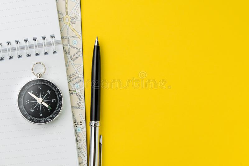 Flat lay or top view of black pen, notepad and map on vivid yellow background table with blank copy space, tourist, vacation or stock photography
