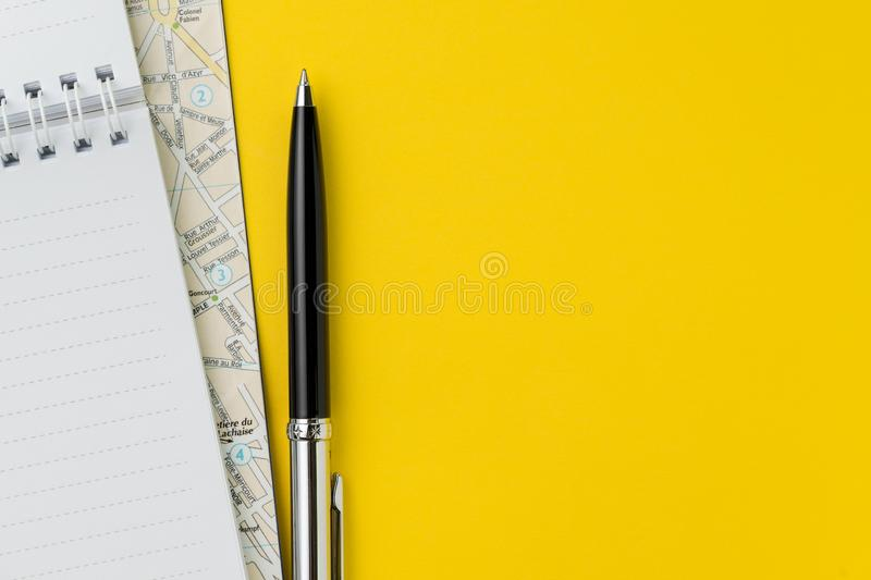 Flat lay or top view of black pen, notepad and map on vivid yellow background table with blank copy space, tourist, vacation or stock photo