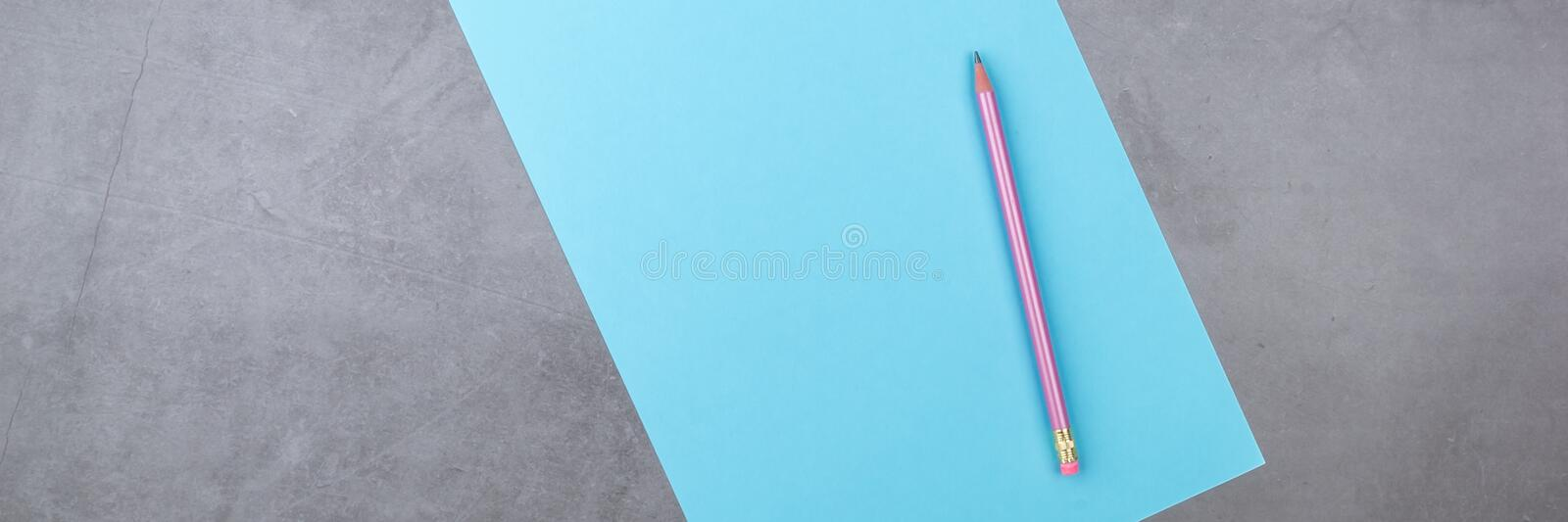 Flat lay, top view, blue sheet and pencil on a gray textured background royalty free stock image
