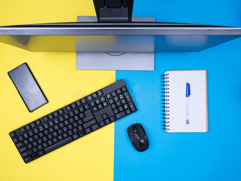 Flat lay top view of business man notebook next to keyboard over blue background. Workplace concept stock photography
