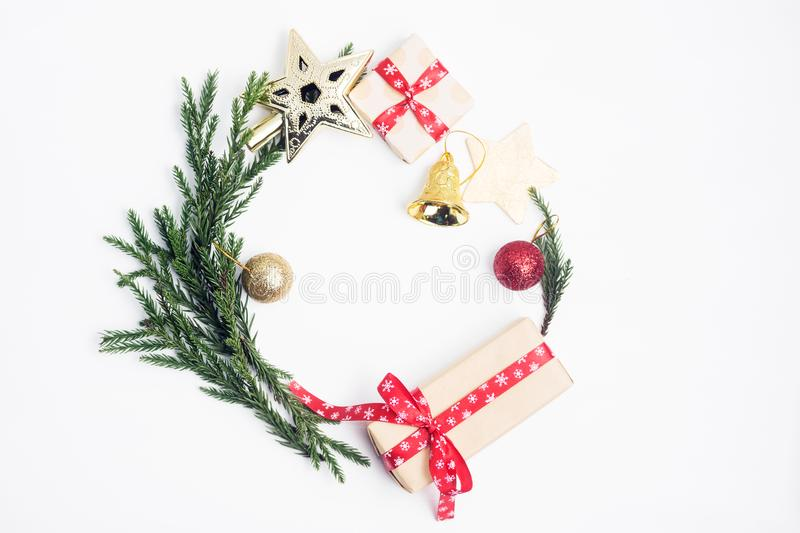Flat lay top view Christmas round frame made of fir branches, toys and gifts stock images