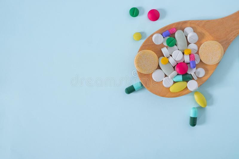 Flat Lay, Top View of Colorful, Assorted pharmaceutical medicine pills. Many pills and tablets in wooden spoon isolated on blue ba stock images