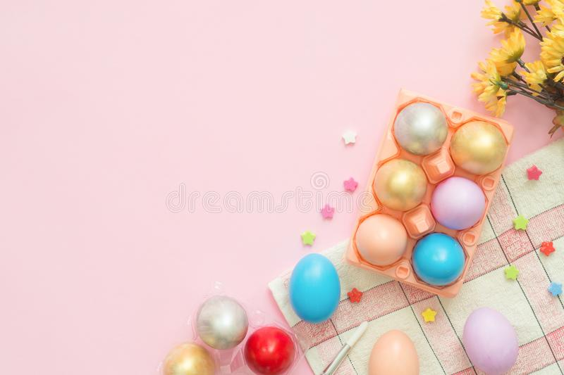 Flat lay top view colorful easter egg painted in pastel colors composition and spring flowers on pink pastel color background. stock photos