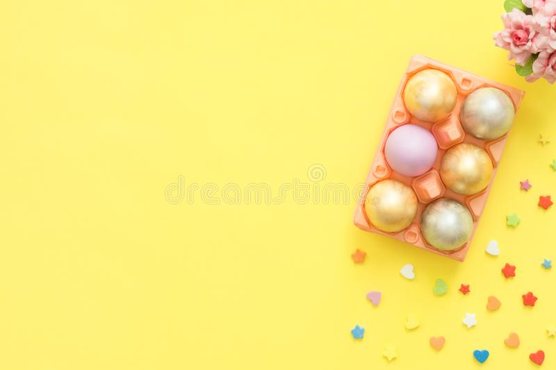 Flat lay top view colorful easter egg painted in pastel colors composition and spring flowers on yellow pastel color background. Easter day background top view stock photos