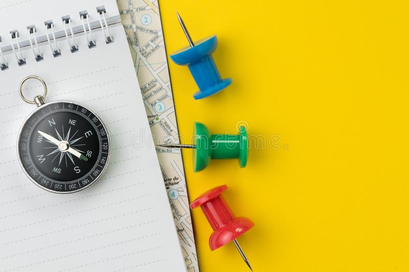 Flat lay or top view of compass on notepad and map with thumbtack on vivid yellow background table with blank copy space, tourist stock photography