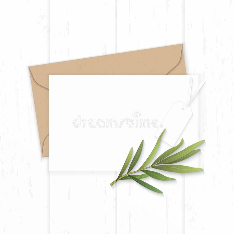 Flat lay top view elegant white composition letter kraft paper envelope tarragon leaf and tag on wooden background. A Flat lay top view elegant white composition stock photo