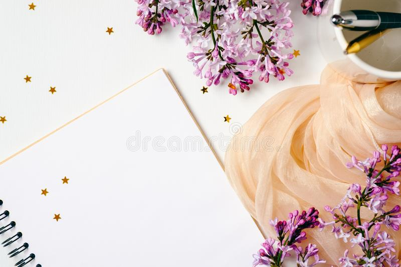 Flat lay, top view female office table desk. Workspace with paper notebook, stationery, purple lilac flowers, orange scarf, stock photo