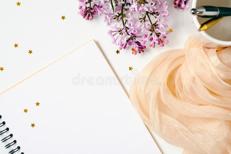 Flat lay, top view female office table desk. Workspace with paper notebook, stationery, purple lilac flowers, orange scarf, royalty free stock photo