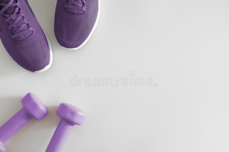 Flat lay top view Fitness accessories on a White background. Purple dumbbells and purple sport shoes on white with copy space. stock image
