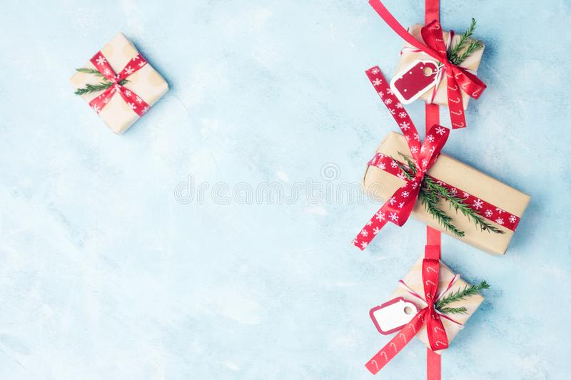 Flat lay top view four christmas gift boxes in craft paper with red ribbons on light blue. Background. New year concept. Text space stock photo